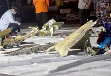 Un trabajador inspecciona los restos recuperados del lugar del accidente aéreo | AFP