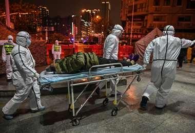 El 21 de enero de 2020 en Wuhán, personal médico auxiliando a un paciente de covid | AFP