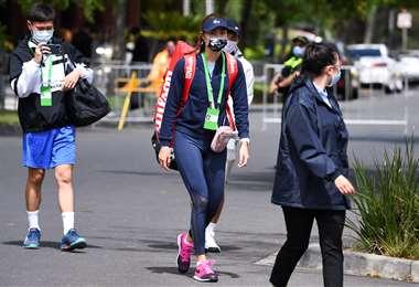 La tenista taiwanesa Chan Hao Ching (c) llega al hotel donde hará la cuarentena. Foto: AFP