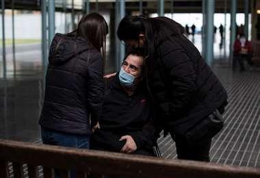 Carlos, con Covid-19, abraza a su esposa a hija. Estuvo 3 meses en UTI/Foto: AFP