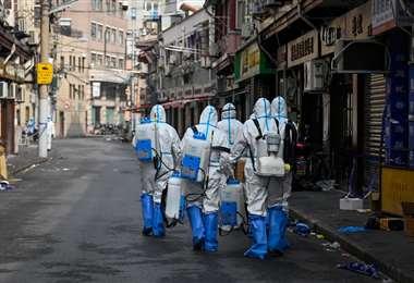 Trabajadores de salud se preparan para rociar desinfectante en un área de Shanghai | AFP