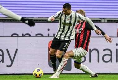 Cristiano Ronaldo se lleva la pelota ante la marca de un rival del Milan. Foto: AFP