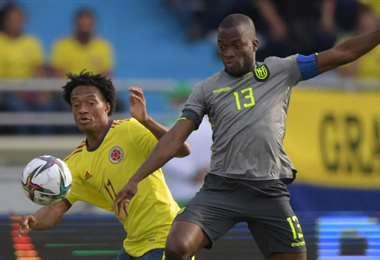 El colombiano Cuadrado (izq.) disputa el balón con el ecuatoriano Valencia. Foto: AFP