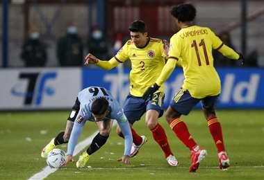 Rodríguez disputa la pelota con Medina y Cuadrado, de Colombia. Foto. AFP