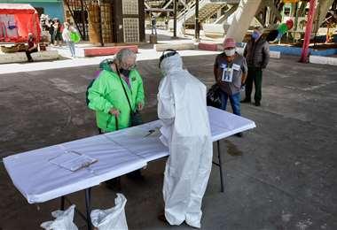 Un trabajador de salud entrega el resultado de una prueba de Covid-19. Foto. AFP