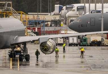 Técnicos revisan el motor afectado del 777. Foto AFP