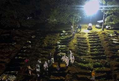 En Brasil realizan los entierros en horas de la noche. Foto AFP