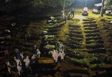Trabajadores de un cementerio de Sao Paulo (Brasil) llevan un ataúd. Foto: AFP
