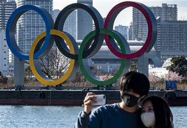 Una pareja posa para fotos frente a los anillos olímpicos. Foto: AFP. Foto: AFP