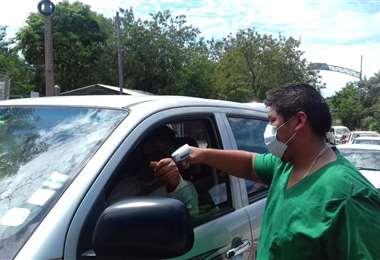Un funcionario mide la temperatura a las personas que ingresan por Puerto Quijarro