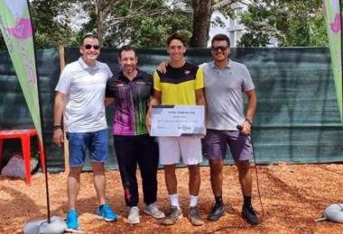 Tenti sostiene el cheque simbólico de su premio y posa junto a organizadores del torneo.