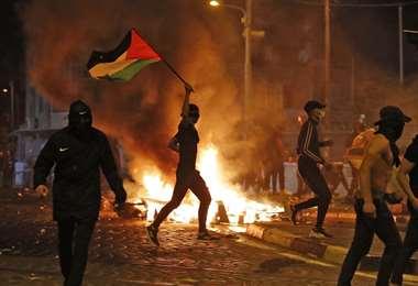 Un palestino hace ondear la bandera Palestina en medio de los conflictos