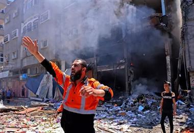 Un bombero palestino trabaja en la escena donde impactó un ataque aéreo israelí