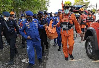 Rescatistas llevan el cuerpo de una de las víctimas del accidente