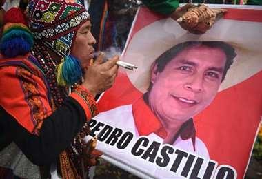 Un chamán fuma junto a un cartel de Pedro Castillo en un ritual para adivinar si ganará