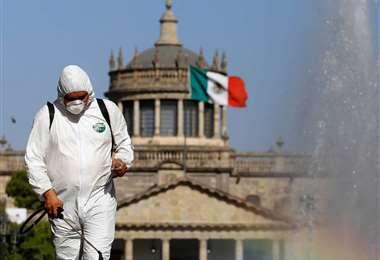 Una persona fumiga una calle en Ciudad de México. Foto. Internet