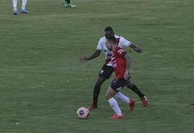 Damiel Lizio se lleva la pelota ante la marca de Enoumbá. Foto: APG