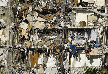 Escombros cuelgan de un edificio parcialmente derrumbado en Surfside. Foto. AFP