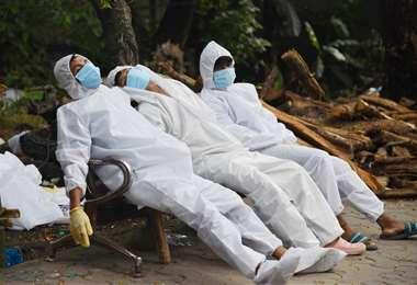 Personal médico toma un descanso en una banca. Foto AFP