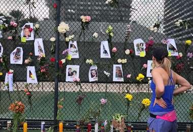 Una persona mira fotografías de algunos de los desaparecidos del edificio de condominios
