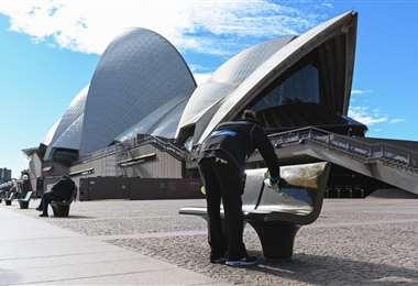 Un trabajador limpia los asientos públicos afuera de la Ópera en Sídney