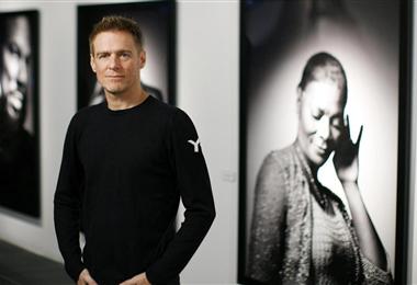 Bryan Adams junto a una de sus fotografías