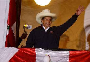 Pedro Castillo saluda a sus seguidores desde el balcón de la sede de su partido. Foto: AFP
