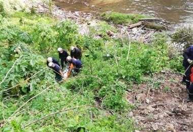 Los policías y peritos de la Fiscalía sacaron del rio el cadáver de la menor el viernes.