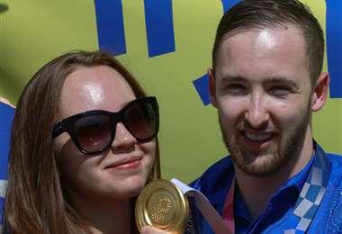 Dolgopyat, que aparece con su novia María Sakovic, muestra la medalla que ganó. AFP