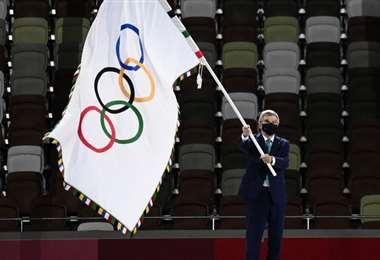 El presidente del COI Thomas Bach ondea la bandera olímpica. Foto: AFP