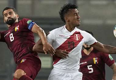 El peruano Tapia (13) intenta dominar el balón ante la marca de Rincón. Foto: AFP